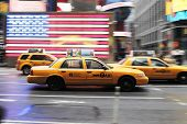 NEW YORK CITY, USA - JUNE 12: Yellow taxi cab speeding through Times Square. A US flag in the background. June 12, 2012 in New York City, USA