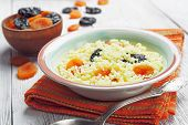 stock photo of prunes  - Millet porridge with dried apricots and prunes in a bowl