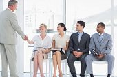 image of beside  - Businessman shaking hands with woman besides people waiting for job interview in a bright office - JPG