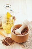 stock photo of flax seed oil  - mortar with flax seeds and linseed oil in glass jug - JPG
