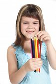 A young girl choosing a colorful crayon. All isolated on white background.