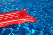 An inflatable red air mattress swimming in a shiny blue swimming pool.