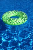 An inflatable green plastic ring swimming in a shiny blue swimming pool.