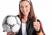 An attractive german soccer fan wearing several fan utensils and holding a soccer ball. All isolated