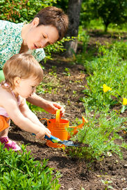 stock photo of mother baby nature  - Mother and her little daughter doing gardening - JPG