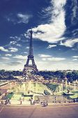 Toned faded view of the Eiffel Tower, Paris looking across the park and fountains with pedestrians a