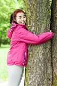 stock photo of mongolian  - Mongolian girl hugging a tree  on a sunny day - JPG