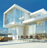 Modern angular whitewashed luxury tropical villa with huge glass windows overlooking a paved patio w