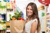 stock photo of local shop  - Healthy positive happy woman holding a paper shopping bag full of fruit and vegetables - JPG