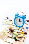 Pile of pills with banknotes and clock isolated with copy-space