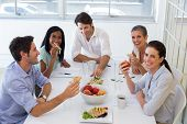 Workers laugh while eating sandwiches for lunch in the office