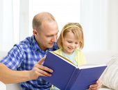 family, children, education, school and happy people concept - smiling father and daughter with book