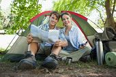 Cute couple sitting by tent reading a map smiling at camera on a sunny day