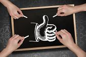 Composite image of multiple hands drawing thumb up with chalk against blackboard