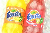 Bottle of Fanta drink on ice cubes.