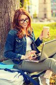 education, technology and internet concept - smiling redhead teenager in eyeglasses with laptop comp