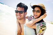 Close up portrait of attractive young couple piggybacking at the beach - soft vintage colors