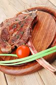 served main course: boned roasted lamb ribs served with green chives and cherry tomato on wooden pla