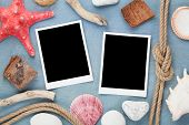 Travel photo frames on blue wooden texture with seashells and rope around
