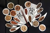 Chinese herbal medicine with yin and yang calligraphy script on rice paper with herb selection. Translation reads as yin yang.