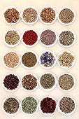 image of wiccan  - Medicinal herb selection also used in witches magical potions in white porcelain bowls over mottled handmade paper background - JPG