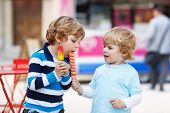 Two Kids Feeding Each Other With Ice Cream