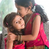 Indian girl kissing her younger sister with love. Asian family at home. Beautiful daughters in traditional India sari.