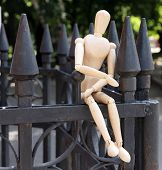 Wooden pose puppet on fence outdoors