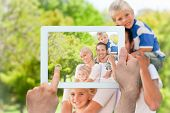 Hand holding tablet pc showing happy family in the park