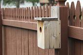 Handmade birdhouse on a picket fence
