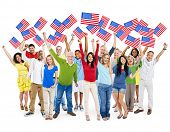 Cheerful Multi-Ethnic Group Of People Standing With Their Arms Raised Holding North American Flag.
