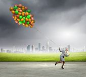 Young businesswoman running with bunch of colorful balloons