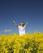 Smiling Woman with Outstretched arms on a Rape Field