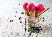 Studio photo of ice cream scoops in waffle cones. Served on wooden planks
