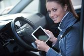 Smiling Woman In A Car With Tablet