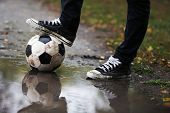 Soccer ball on ground in rainy day, outdoors