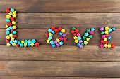 Inscription LOVE made of p decorative paper stars on wooden background