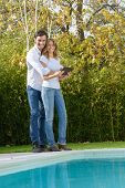 Romantic couple looking at a digital tablet standing by the pool