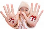 Happy girl demonstrating painted Christmas symbols on her hands. Santa Claus, Christmas tree, Snow