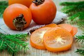 Fresh Organic Persimmon With Slices On Wooden Background