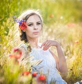 Young girl on golden wheat field.Portrait of beautiful blonde girl with wreath of wild flowers
