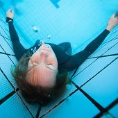 Female Diver With Eyes Closed Underwater In Swimming Pool