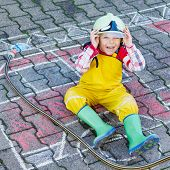 Funny Adorable Child Of Four Years Having Fun With Fire Truck Picture Drawing With Chalk.