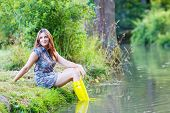 Young Beautiful Woman Sitting In Yellow Rain Rubber Boats By A River In Summer