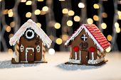 holidays, christmas, baking and sweets concept - closeup of beautiful gingerbread houses on table over black garland lights
