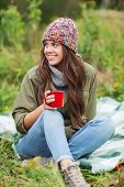 adventure, travel, tourism, hike and people concept - smiling young woman with cup sitting in camping