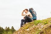 adventure, travel, tourism, hike and people concept - man with backpack sitting on ground and looking far away