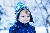 Portrait Of Little Child In Winter Clothes With Falling Snow