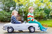 Two Happy Twins Playing With Big Old Toy Car In Summer Garden, Outdoors