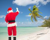christmas, holidays, travel and people concept - man in costume of santa claus writing something from back over tropical beach background